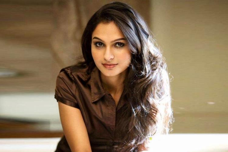 Andrea Jeremiah is seen wearing a brown shirt striking a pose in the image