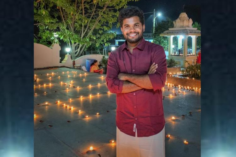 Anil Geela standing in a temple wearing traditional dress amidst lamps