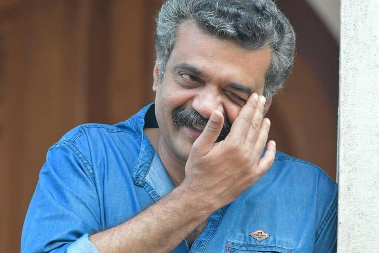 Anil in a blue shirt and a grey-black hair smiles a hand touching his left eye