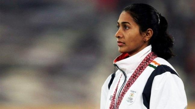 Anju Bobby George in white standing in front of a stadium