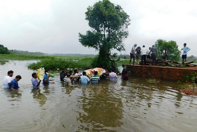 Residents of Ktaka village brave chest-high water to cremate dead body