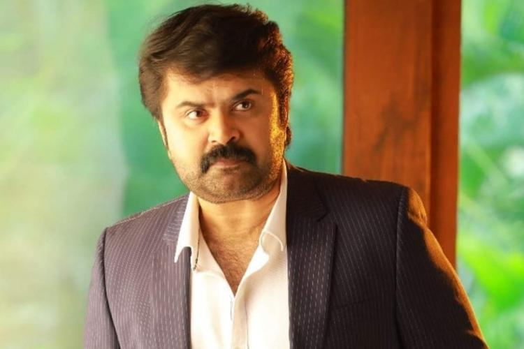 Anoop Menon is seen wearing a navy blue coat and staring in the image
