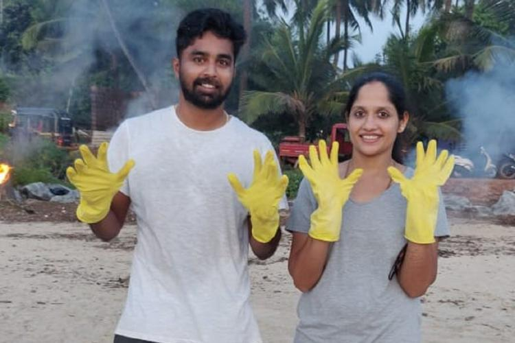 A couple wearing cleaning gloves on their hands at Someshwara beach