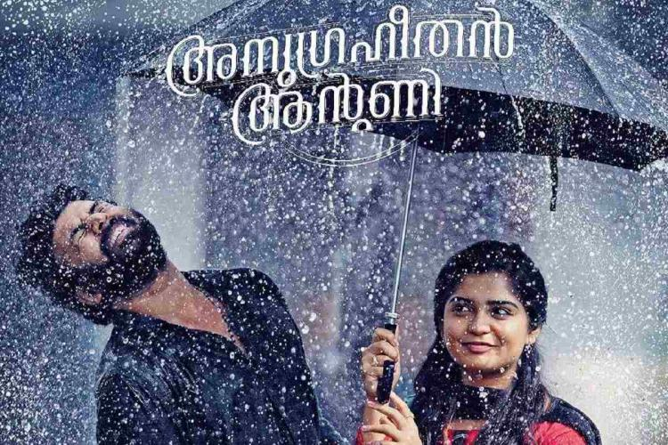 A bearded man and a young woman are in the rain The woman is holding an umbrella and smiling and the man is just out of the umbrella shaking his head and laughing