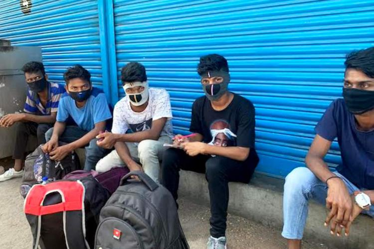 Migrant workers in Chennai wait outside a shuttered shop