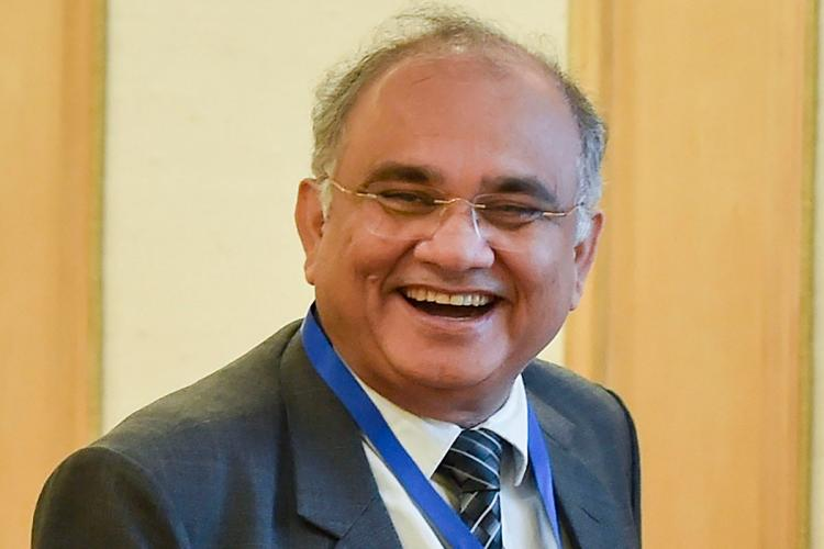 Anup Chandra Pandey in a suit smiling