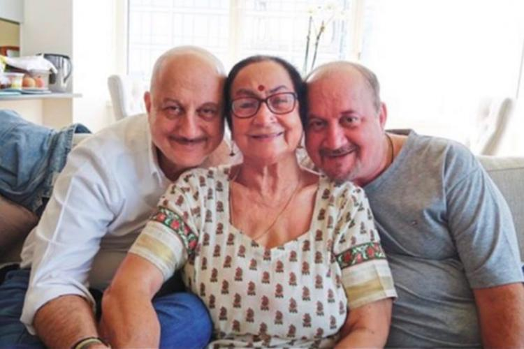 A picture of Anupam Kher sitting with his mother Dulari and brother Raju