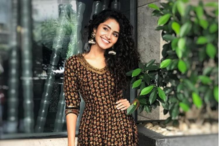 Anupama in a dark brown kurti standing against a glass window a hand on her hip smiling