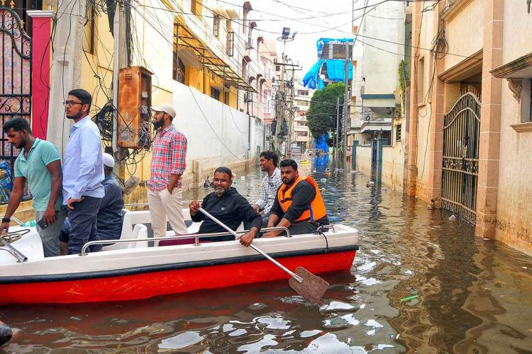 People were seen evacuating from the flood hit areas in a red coloured boat in the middle of colony roads
