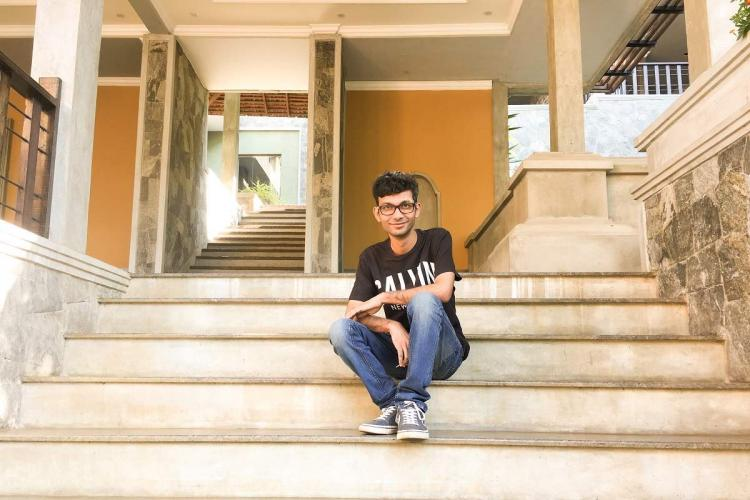 Appu sits wearing a t shirt and jeans on the steps in front of a building