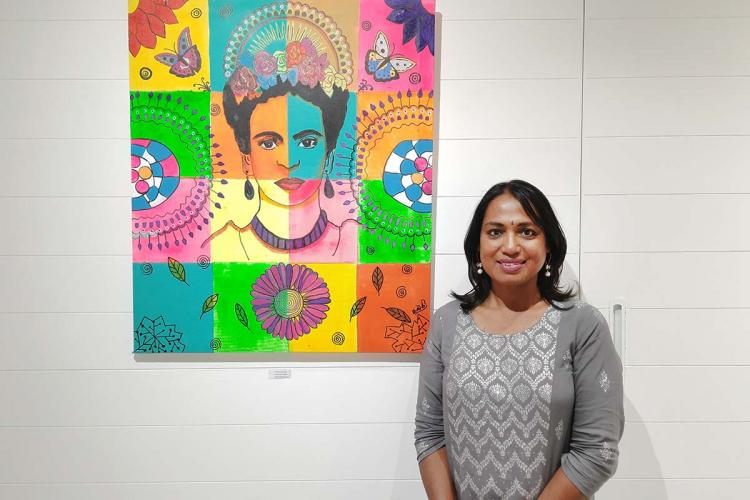 Kalki Subramaniam standing with a portrait of Frida Kahlo