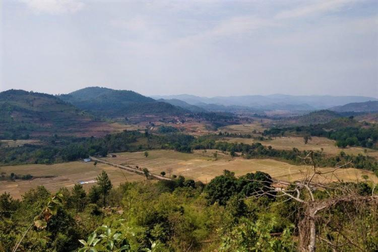 A wide shot of the Araku valley with hills in the distance and trees and empty land