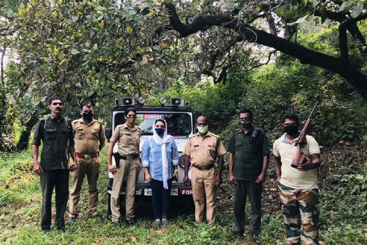 Officials of the forest department standing in a forest region One of them is holding a gun