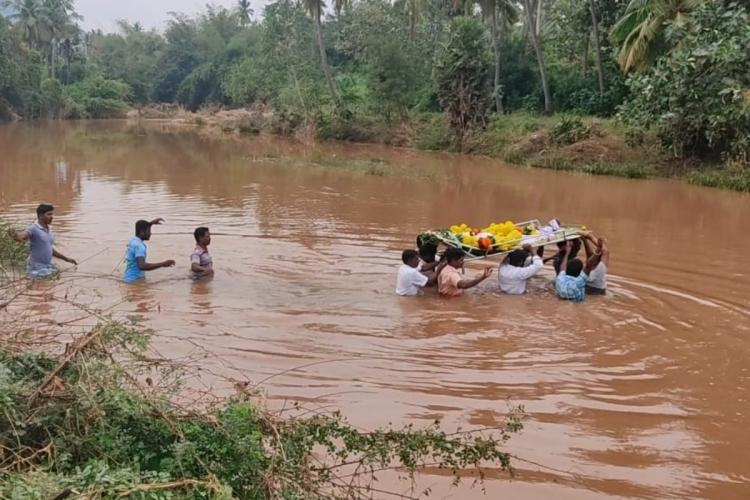 Villagers taking a corpse for burial by crossing a river in Kamandalapuram