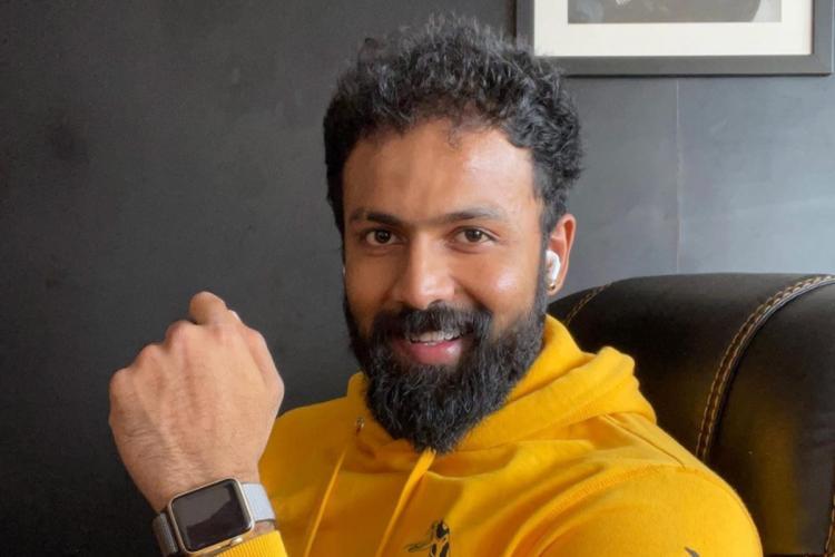 Arjun Gowda is seen wearing a yellow sweatshirt in the image