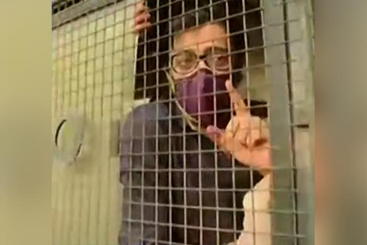 Arnab Goswami points from inside a police van after he was arrested by the Mumbai police in an abetment to suicide case