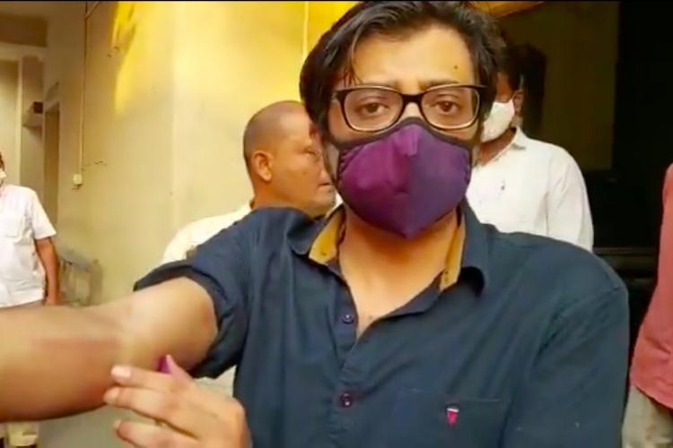 Arnab Goswami pointing at his arm after being arrested by the Mumbai and Raigad police in connection with a 2018 suicide case