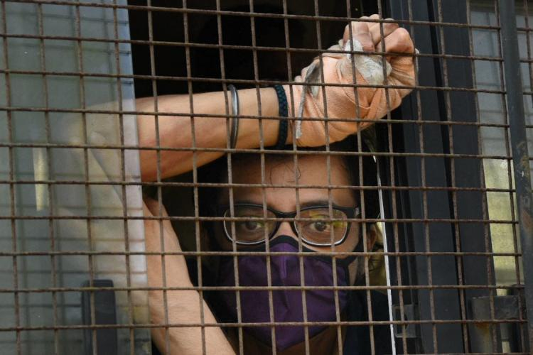 Arnab Goswami sits in a police van wearing a mask after being arrested in Mumbai