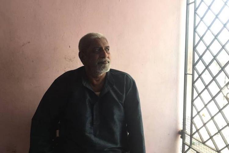 Art director P Krishnamoorthy seated next to a grilled gate wearing a dark blue kurtha