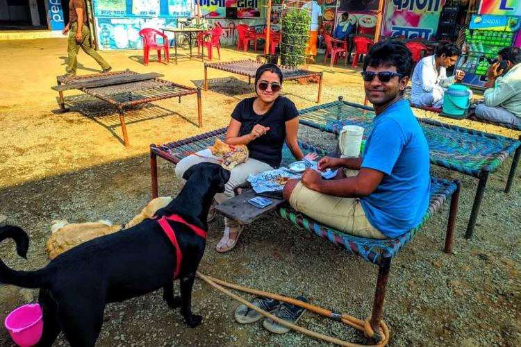 Arun Sekhar with wife Rimjhim and pets resting outside a dhaba