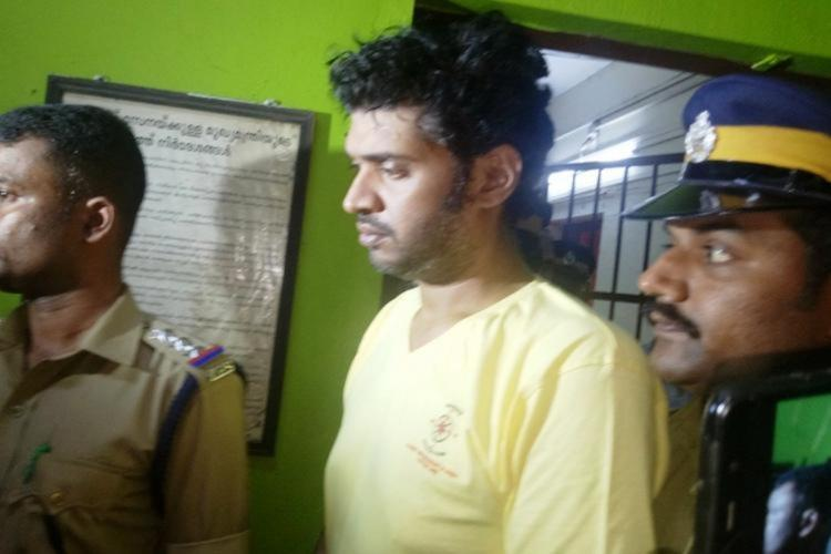 Accused Arun Anand who is seen wearing a yellow t-shirt was arrested in April 2019 He is flanked by two police officials Arun is accused of brutally assaulting his partners seven-year-old son which caused his death