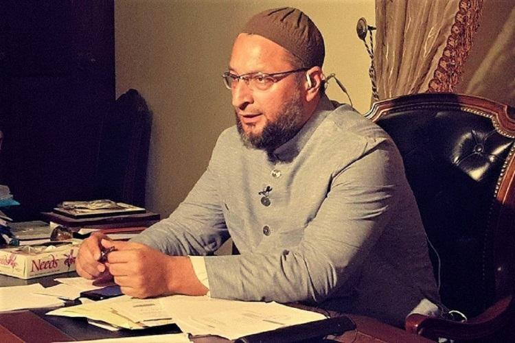 Asaduddin Owaisi in a brown cap looking away from the cam and seated at a table
