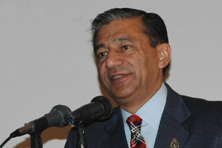 Former CBI director Ashwani Kumar wearing a suit and tie speaking into a mic at an event