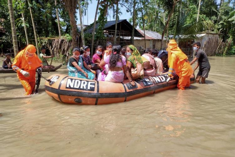 Rescue operation on in Kamrup district of Assam NDRF officials in orange hazmat suits are pushing a boat full of people through flood water in Assam