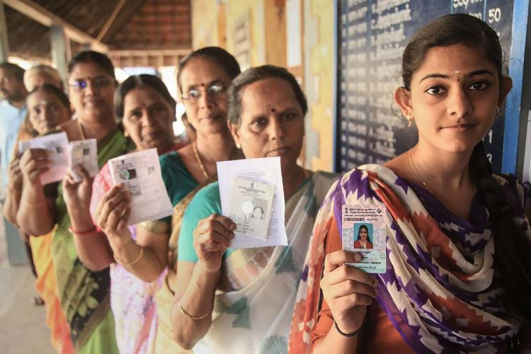 Women standing in line to vote and holding up their Voter IDs