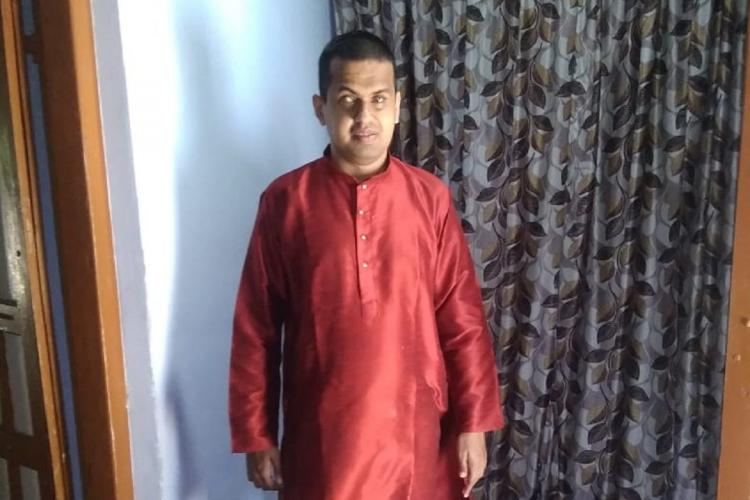 Aswin, a bling man, stands in a room wearing a red kurtha