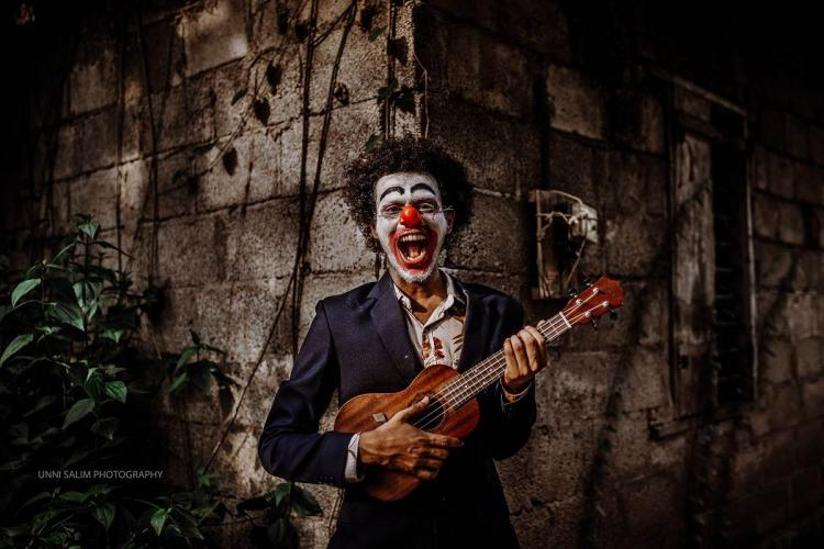 Athul wearing a clowns makeup and playing a ukulele in a dark background