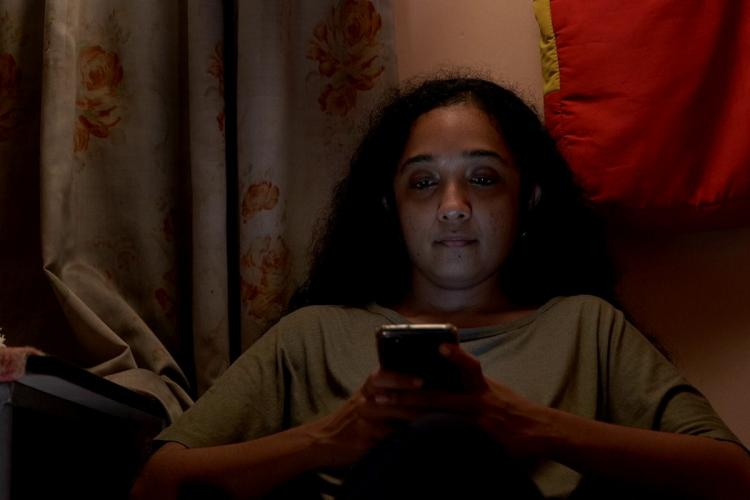 Archana sits in a dim lit room wearing a lose t shirt and looking at her phone with her hair let lose