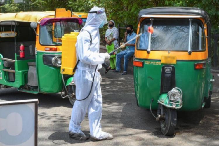 Health worker sanitizing an auto rickshaw