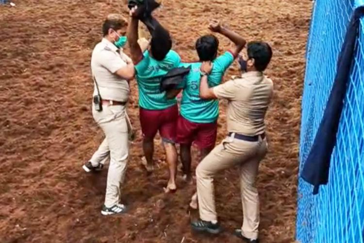 Police officers in Madurai detaining bull tamers who shouted anti-farm law slogans
