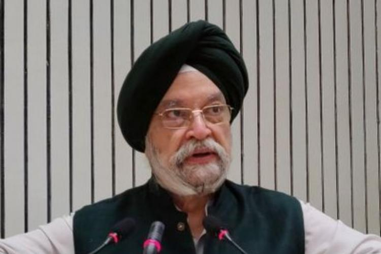 Aviation Minister Hardeep Singh Puri speaking into a mic He is wearing a black vest and black turban