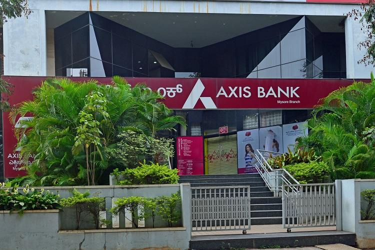 Picture of bank building with board saying axis bank and green trees on either side of the entrance
