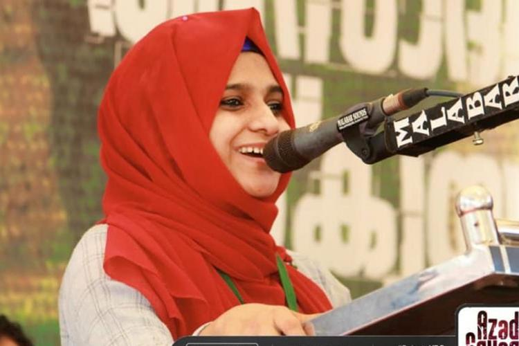 PH Ayisha Banu, who is wearing a headscarf, stands at the podium and speaks into the mic.