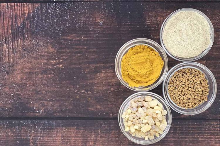 Four bowls containing turmeric Boswellia Ashwagandha and Fenugreek ingredients of Ayurvedic medicine