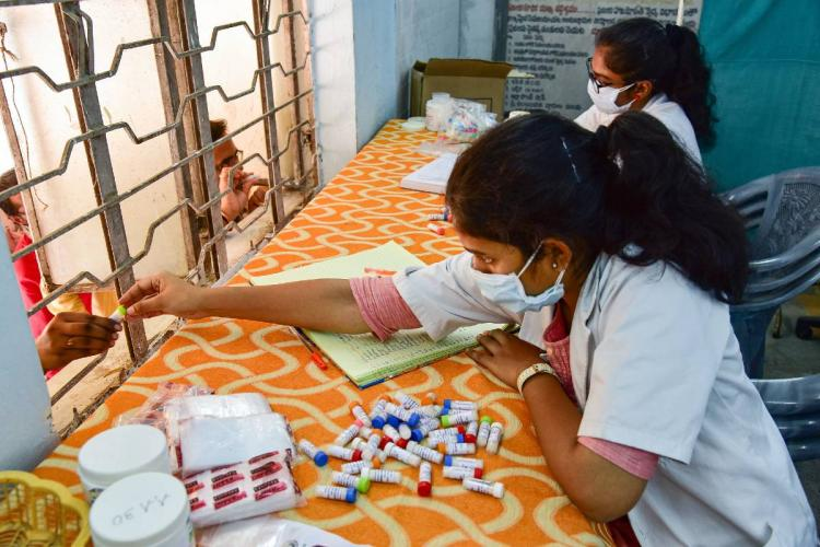 A doctor distributes homeopathy medicine claimed to prevent COVID-19