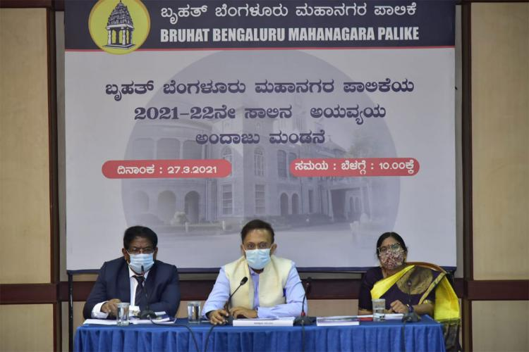 Three seated BBMP officials announcing the 2021-22 budget