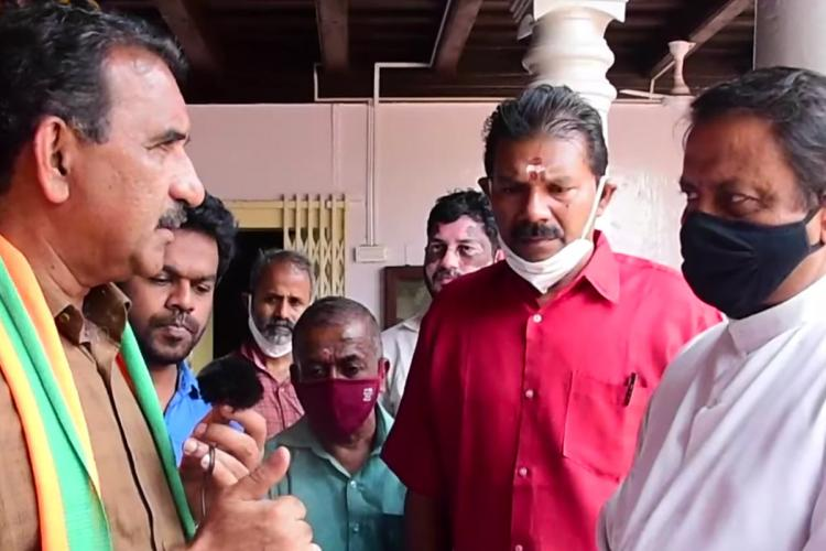 A screenshot from the video where Ollur BJP candidate B Gopalakrishnan left in brown shirt is appealing to a Christian priest to vote for the BJP Other party members are seen standing around Gopalakrishnan and the priest