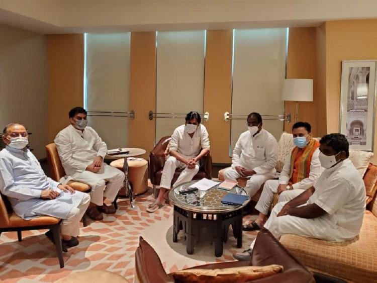BJP and JanaSena leaders sit together in sofas arranged in a round table manner in a hotel wearing Kurthas and shirts
