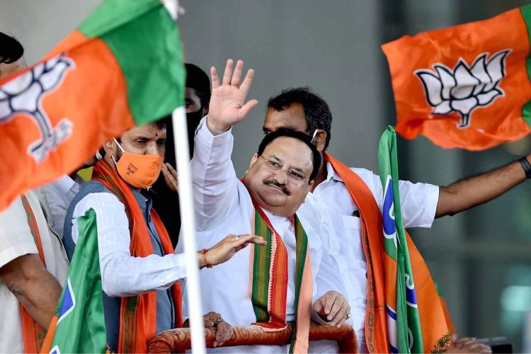 BJP President JP Nadda waving his hand. He is standing amidst other party leader.