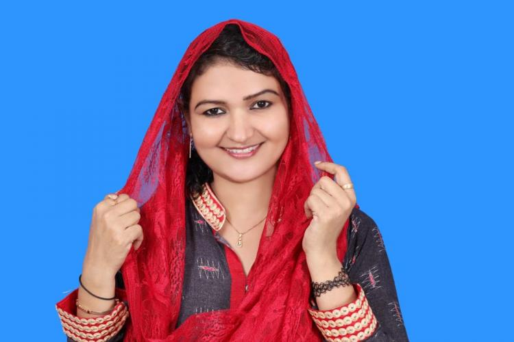 BJP candidate TP Sulfath in a navy blue kurta and a red dupatta draped over her head She is smiling at the camera