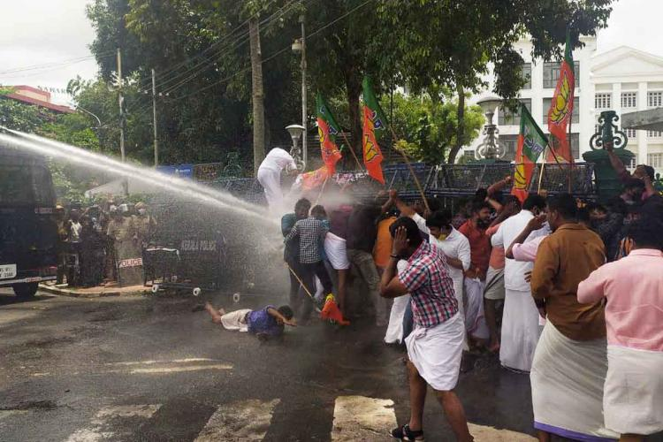 Protestors trying to jump over the barricades in front of Kerala Secretariat. Police can be seen using water cannons at the protestors.