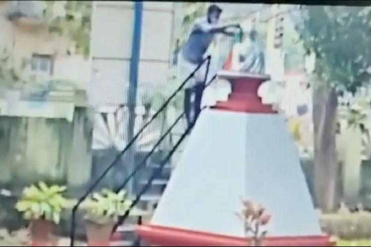 Screengrab of man on top of a set of steps draping a flag around Mahatma Gandhis statue