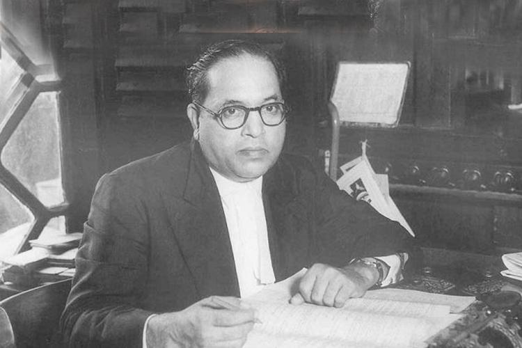 Black and white photo of BR Ambedkar sitting at a table with papers in front of him