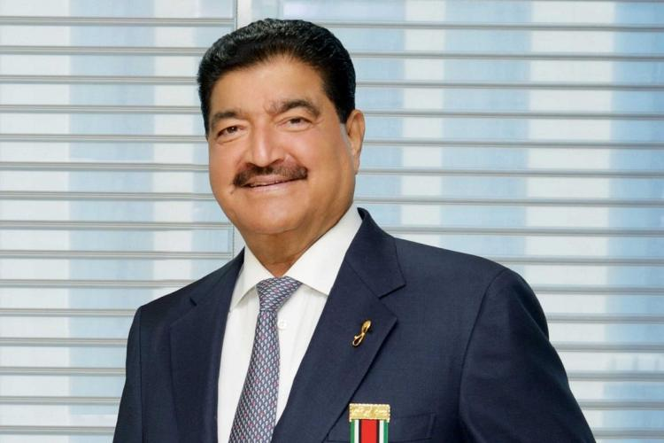 BR Shetty posing for the camera in a suit against a blue background