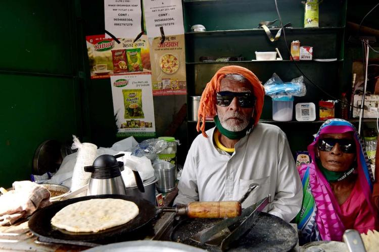 80-year-old Kanta Prasad and Badami Devi serve food at Baba Ka Dhaba, nearly a month after its owners plight became viral on social media and revived their livlihood amid coronavirus pandemic, at Malviya Nagar in New Delhi, Friday, Oct. 30, 2020.