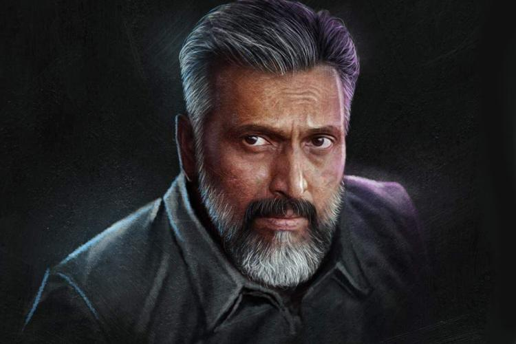 Babu Antony with a grey and black beard and hair against a grey background and wearing grey
